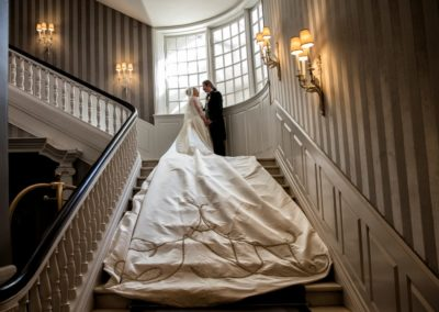 The Reception: The newly wed couple on the d'Angleterre staircase, displaying the their hand-embroidered monogram on the train of the dress.